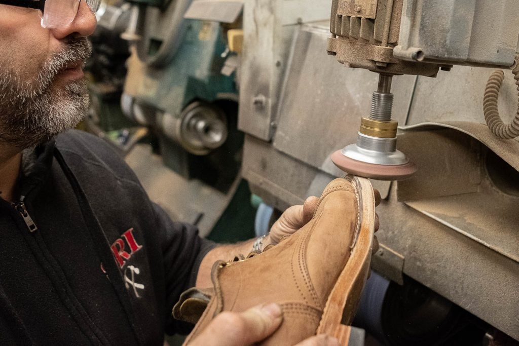 steve doudaklian using a machine to sand down the edges of the welt, midsole, and metal toe tap so they are flush resulting in a fresh new layer of the midsole and outsole edge